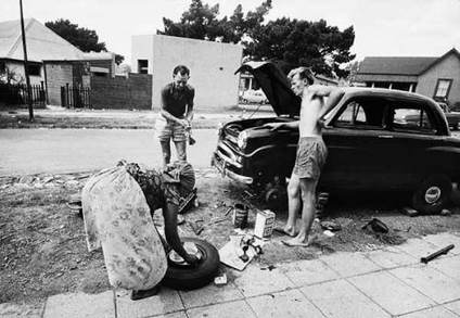 Afternoon tea being served to two men repairing a car on a sidewalk in Fairview, Johannesburg