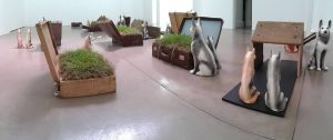 Kemang Wa Lehulere, reddening of the greens or dog sleep manifesto, 2015. Suitcases, earth, grass, blackboards, salvaged school desks (wood), ceramic dogs. Dimensions variable