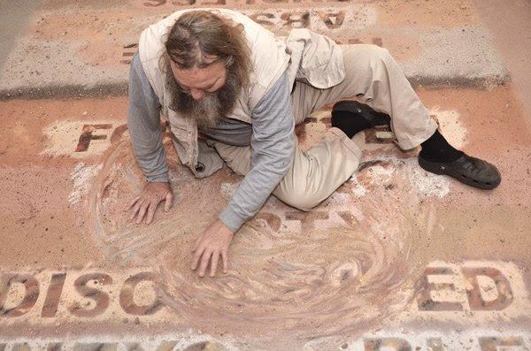 Willem Boshoff erasing the work <i>Book of Sand, Mbombela</i>, 2015