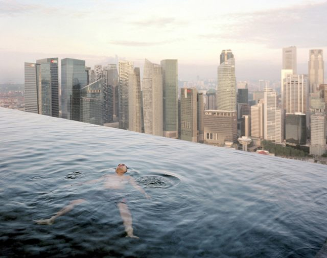 Paolo Woods & Gabriele Galimberti, A man floats in the 57th-floor swimming pool of the Marina Bay Sands Hotel, with the skyline of the Singapore financial district behind him, 2013.