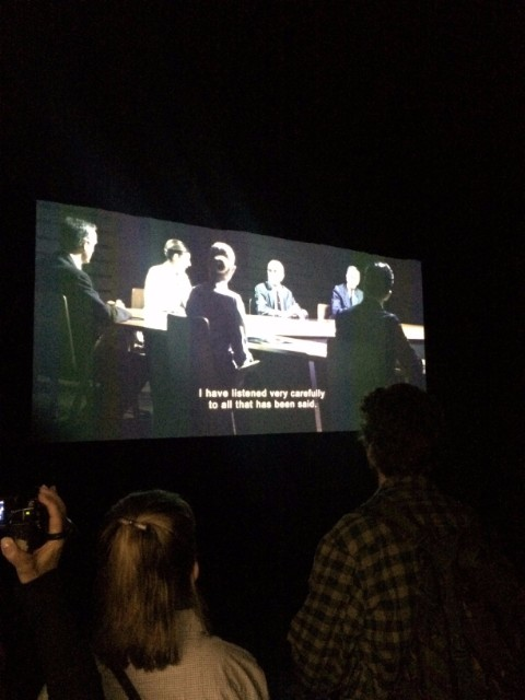 "Visitors huddled in the dark, disorientating space, watching one of several videos within the exhibition. ""Laboratory of Dilemmas focuses on the play's dilemma through the excerpts of an unfinished documentary in the form of found footage about a scientific experiment."""