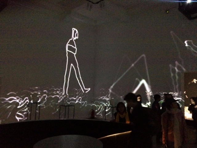 In the next room, various sculptures line the walls. Every few minute, the room darkens and a 360 degree projection animates the marching figures from the previous work, also featuring exploding buildings and other characters.