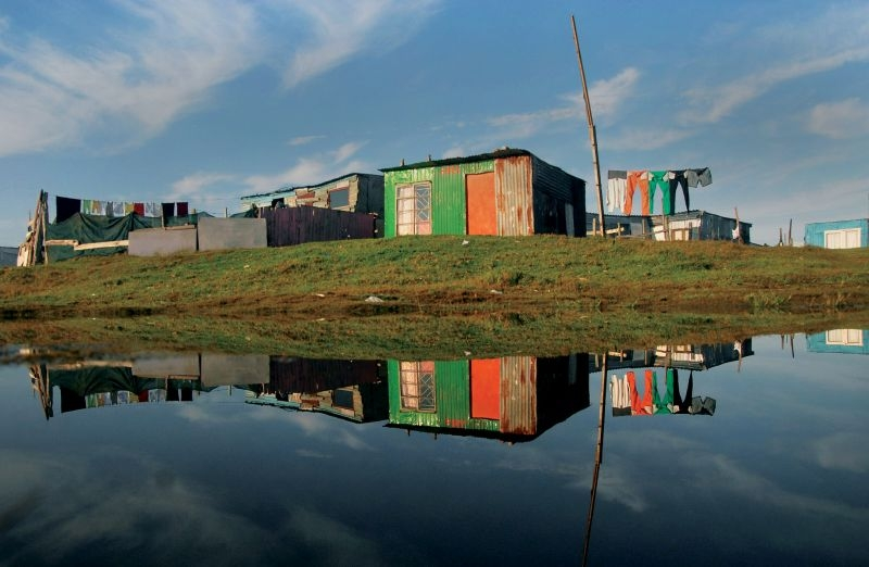 Masixole Feni Cape Town: A pool of water reflecting shack houses after a heavy rain over the Weekend, in Mfuleni Informal Settlement, 2015